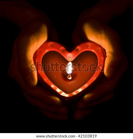 Hands holding heart candle.