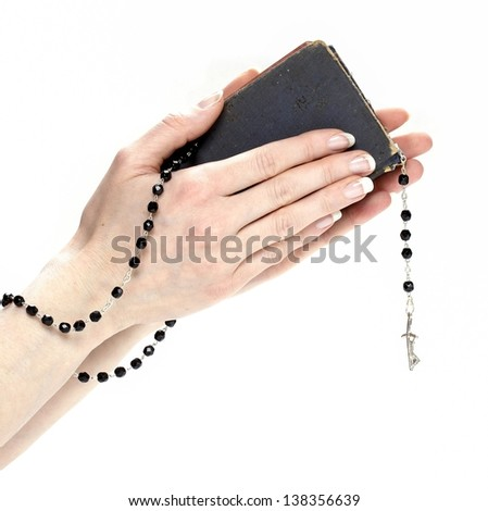 Hands holding Holy Bible and black rosary isolated on white background.