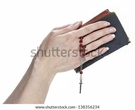 Hands holding Holy Bible and red rosary isolated on white background.