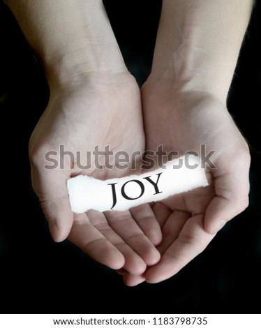 Hands holding joy word sign on paper illustrating choosing to be happy #1183798735