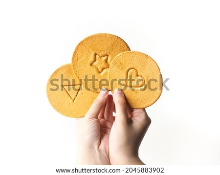 hands holding Korean Dalgona honeycomb candy toffee on white background