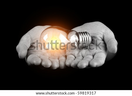 Hands holding light bulb isolated on black
