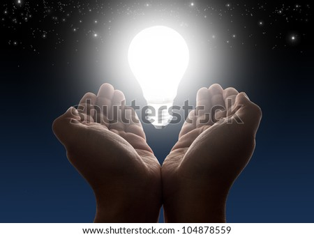 Hands holding light bulb with night sky and stars in background