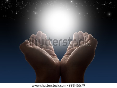 Hands holding light with night sky and stars in background