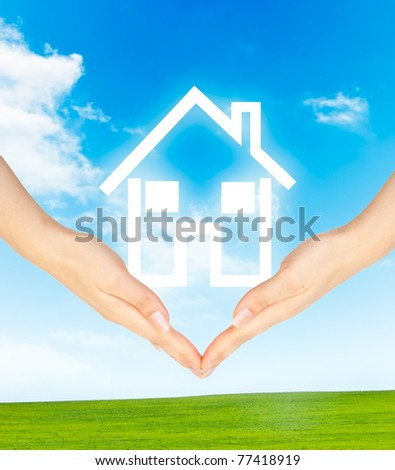 Hands holding model of a house on nature background