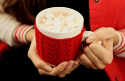 Hands holding mug of hot chocolate with marshmallows close-up