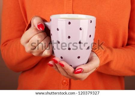 hands holding mug of hot drink, close-up