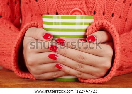 hands holding mug of hot drink, close-up - stock photo