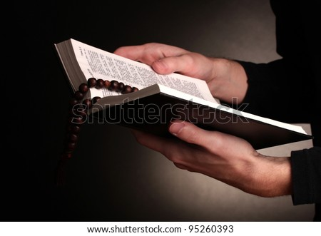 Hands holding open holy russian bible