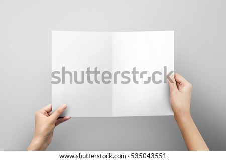 Hands holding paper blank a4 size for letter paper on grey  background.