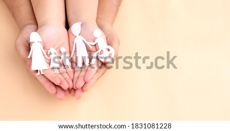hands holding paper Cutout of different family members being together.
