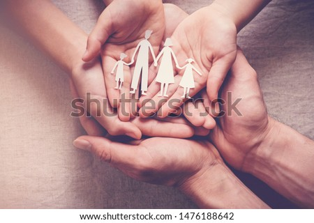 hands holding paper family cutout, family home,adoption,foster care, homeless charity, family mental health, social distancing, homeschooling education, Autism support,domestic violence