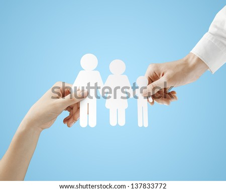 hands holding paper family  on a blue background