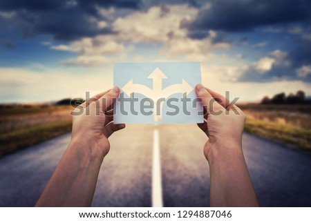 Hands holding paper with arrows crossroad symbol splitted in three different directions. Choose the correct way between left, right and front. Difficult decision concept, over asphalt road background. #1294887046