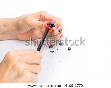 Hands holding pencil and sharpening with Sharpener on white background