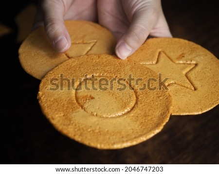 hands holding pieces of Korean Dalgona or Ppopgi honeycomb toffee sugar candy with circle, star and triangle shape