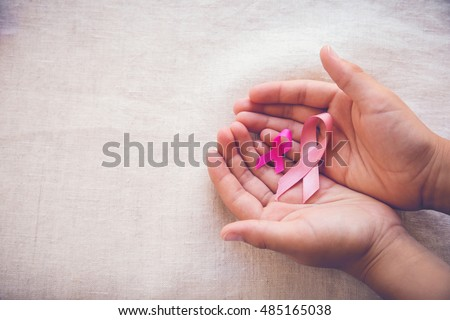 Hands holding Pink Ribbons toning background, Breast cancer awareness and Abdominal cancer awareness #485165038