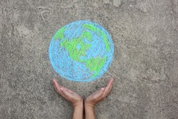 Hands holding planet Earth with copy space (drawing with chalk)