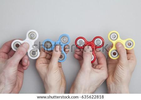 Hands holding popular fidget spinner toy