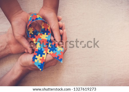Hands holding puzzle ribbon for World Autism Awareness Day, pride, jigsaw #1327619273