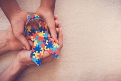 Hands holding puzzle ribbon for World Autism spectrum disorder Awareness Day, pride, jigsaw