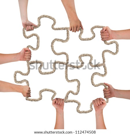 Hands holding rope forming puzzle pieces - stock photo