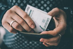 Hands holding russian rouble bills and small money pouch. Toned picture