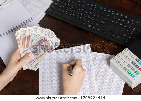 Hands holding Russian rubles at the Desk in the office. Russian Russian cashier Manager at the workplace in a Russian Bank.Issuing salaries, pensions and unemployment benefits in Russia
