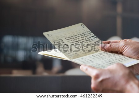 hands holding saving account passbook, book bank on a bank office background