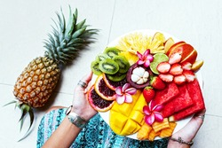Hands holding served fruit plate, top view from above. Exotic summer diet. Tropical beach lifestyle.