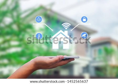 hands holding smart phone with app smart home on blurred house as backgrounds