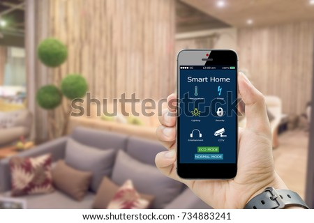 hands holding smart phone with app smart home on blurred living room as backgrounds