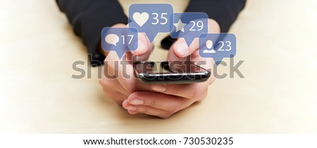 Hands holding smartphone with social media or social network notification icons #730530235