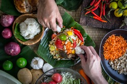 Hands holding sticky rice to eat with Thai papaya salad or what we call