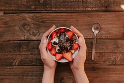 hands holding strawberries with yogurt chocolate pumpkin seeds chia sunflower seeds and apple in a white bowl on a wooden table
