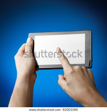Hands holding Tablet PC on blue
