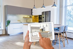 Hands holding tablet with kitchen interior sketch. In background real finished kitchen interior design. Kitchen presentation. Dinning table. Home Interior Design Software Programs.Project management.