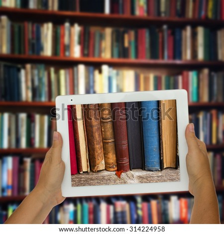 Hands holding  tablet with row of books on screen, library shelfs in background, e-learning concept
