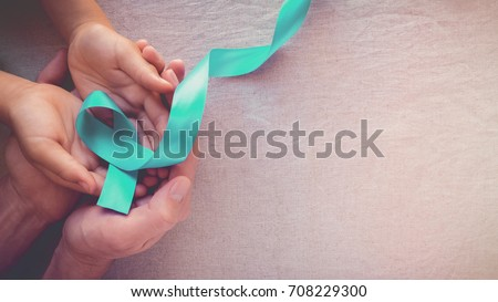 hands holding Teal Ribbon, toning panoramic banner background, Ovarian Cancer, cervical Cancer, pcos and sexual assault awareness