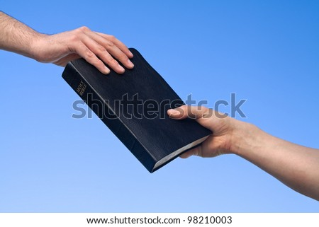Hands holding the Bible over blue sky