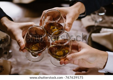 Hands holding the glasses of brandy. Close-up of glasses with cognac in people's hands. Toasting for holiday