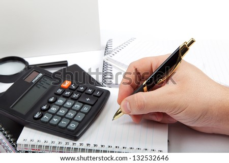 Hands holding the handle and pressing calculator buttons over documents