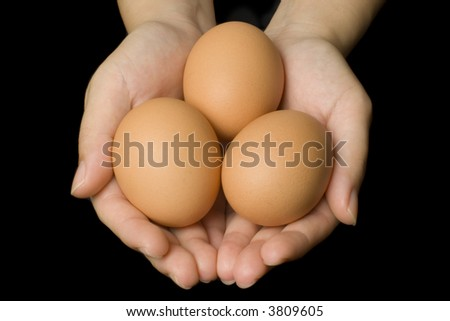 Hands holding three eggs isolated on black background