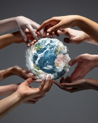 Hands holding, touching planet Earth, close up on grey background. Environment save, taking care of nature and ecology, supporting hands concept. Globe woldwide protection, traveling. Beauty.