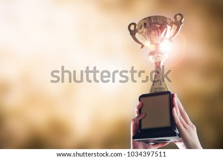 Hands holding trophy cup on gold blurry bokeh background. #1034397511