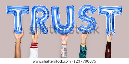 Hands holding trust word in balloon letters #1237988875