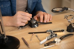 hands holding tweezers repairing vintage clocks