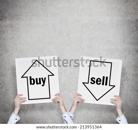 Hands holding two banners - the choice of choice \'sell or buy\'.