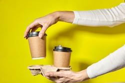 Hands holding two cups brown paper with black lid. Two coffee special offer or promo. Hands holding two cups on yellow screen background. Tea or Coffee to go. Brown paper cup with black lid.