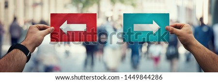 Hands holding two different colored paper sheets with arrows going to left and right directions over a crowded street background. Correct choice concept, taking the right decision, failure or success